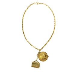 CHANEL Long Necklace in Gilt Metal with Bag and Hat Pendant
