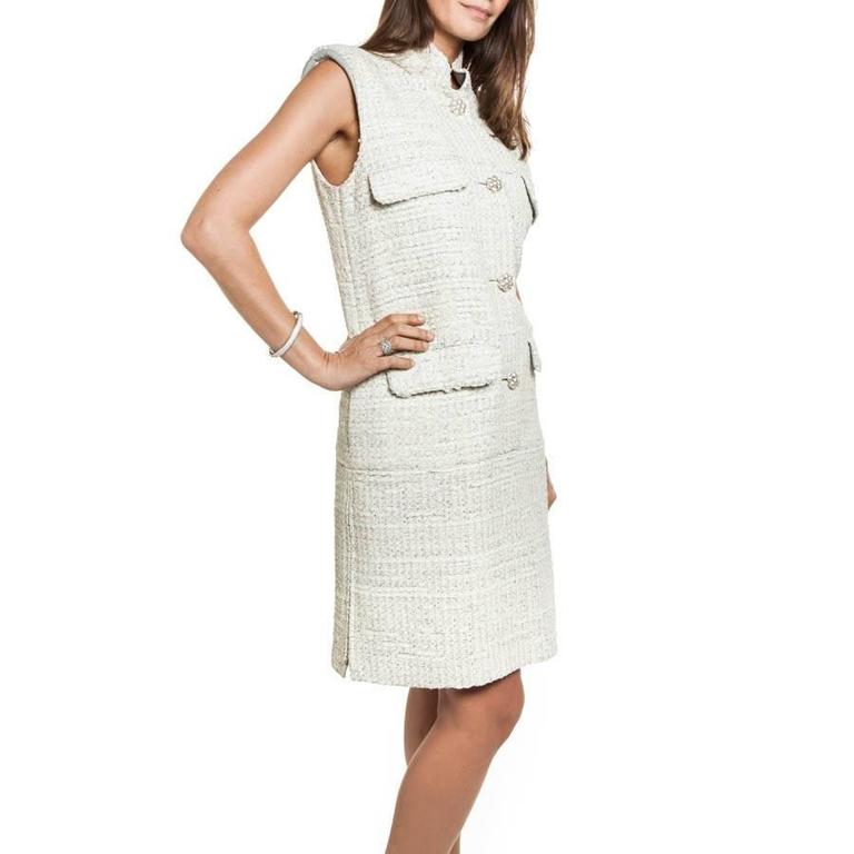 CHANEL sleeveless dress in cream painted tweed.  It closes at the front with 5 beaded buttons in the form of camellias CC.  2 gray leather lapel cuffs on the chest and 2 gray leather lapel pockets at the front at the bottom of the dress.  It has 2