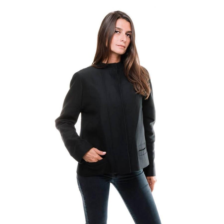 Balenciaga jacket in black gros grain. It has 2 pockets on the sides and closes with 6 buttons coated with coarse grain. In the back a large hollow pleat concealing 2 straps closed by a button.  The lining is made of black silk  Dimensions :
