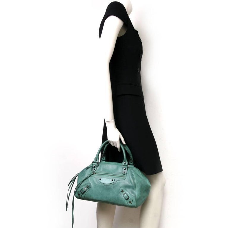 Balenciaga green leather bag with aged brass hardware. Very original closure by a zipper and two magnets folding and masking the latter.  Impeccable interior.  Light spots scattered on the bag (front, back, top). Slight lighter marks on the front of