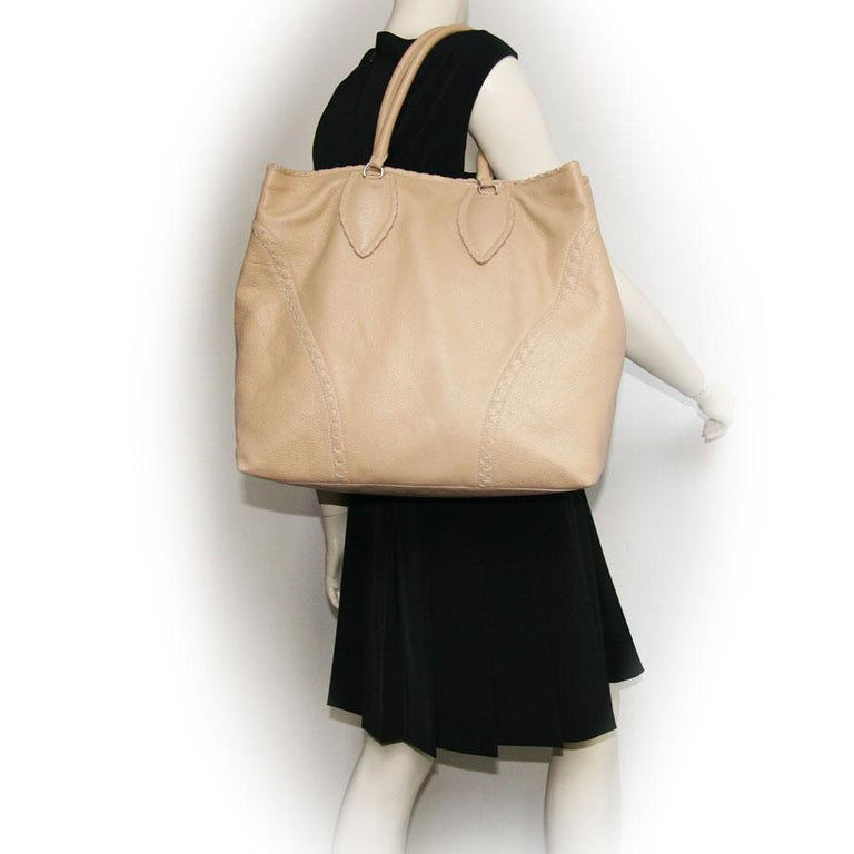 Alaïa Large tote bag in beige grained leather.  The interior is in leather with 3 pockets including: one zipped, one that closes with a zip and the other with a pressure. Worn by hand and arm with two handles that each measure 47 cm.   In very good