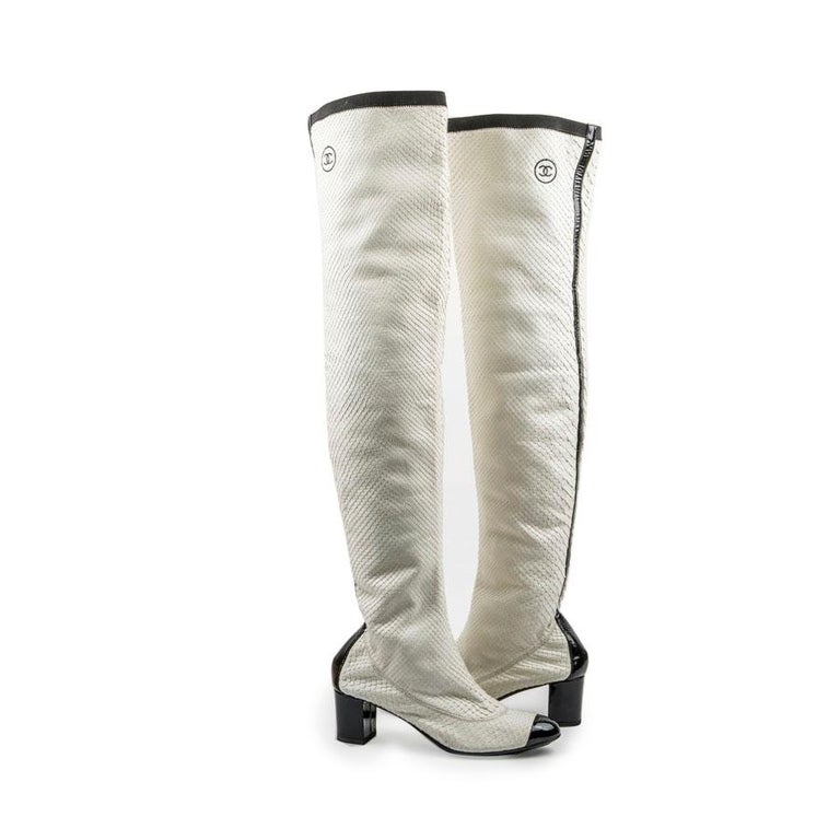 Chanel thigh boots in white python. They are lined in white leather. Black patent leather tip. Black leather band at the back of the shoe. Acronym 'CC' stitching at the top of the boot. The heel is covered with black patent leather. Outsole and