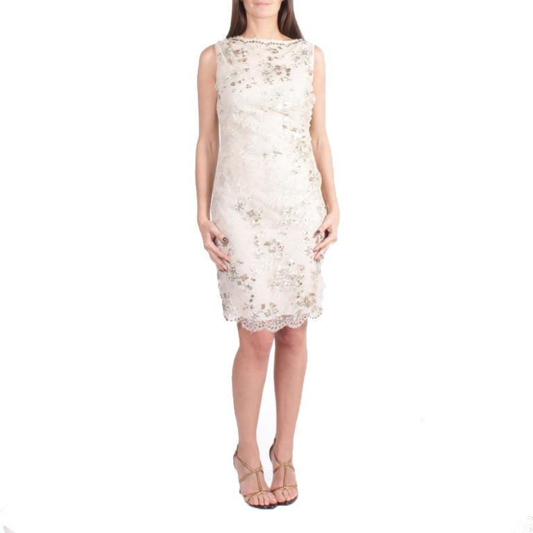 Elegant VALENTINO sleeveless cocktail dress in silver lace embroidered with metallic sequins lined (2 times) with beige silk chiffon, draped on the left side.  It closes with a zipper on the right side. Size 36FR. Made in Italy.  In very good