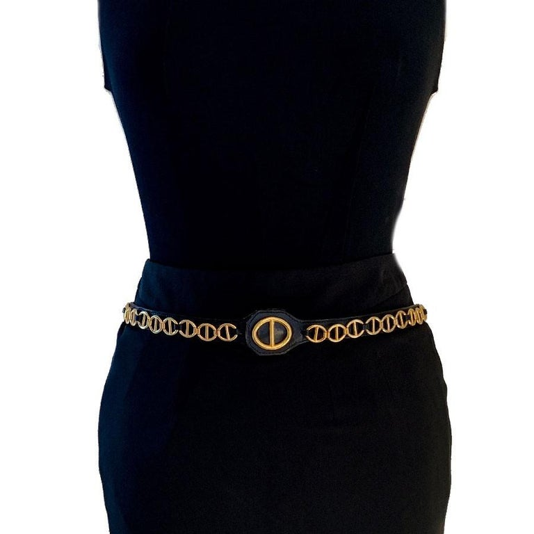 Pretty CHRISTIAN DIOR vintage belt in black calfskin on which there is a chain in gilded metal. The pattern of the chain is found on the all-leather buckle as well.  This thin belt can be worn with pants, a dress or a jacket to mark your size. The