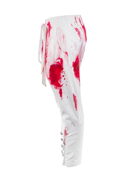2010 Couture Josephus Thimister Moujik Trousers featuring a drop crotch waist with red paint stains. Has button tapered ankles, elastic back waistband, drawstring front waistband, and a folded front seam. New with Tag.