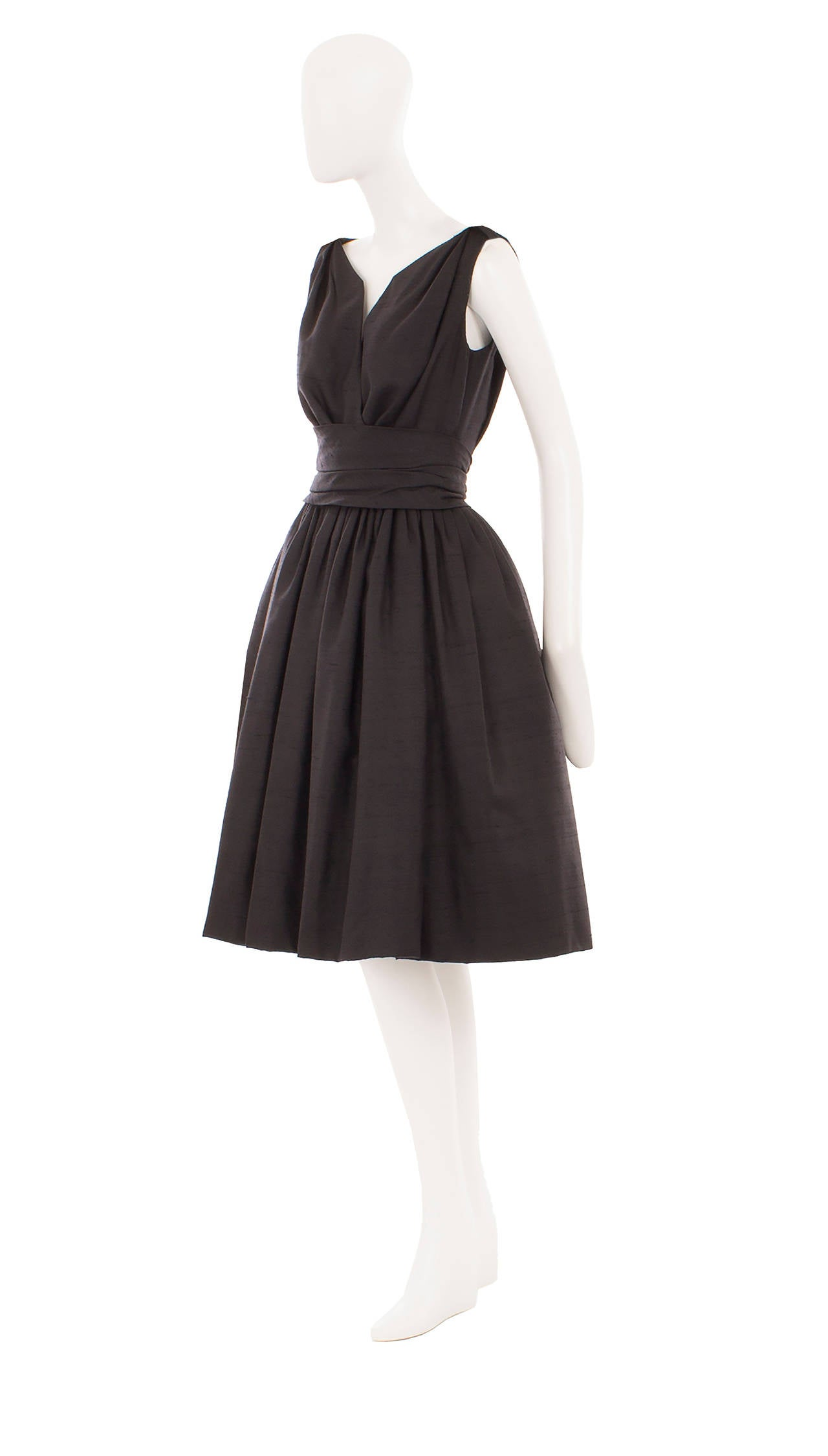 This classic Christian Dior little black dress is perfect for cocktail parties and special events. Constructed in soft silk Dupion, the dress features a plunging neckline and bow detail on the shoulders. A pleated waistband cinches in and