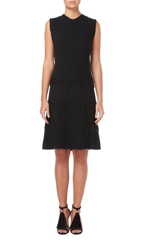 An incredibly chic cocktail option, this haute couture Carven dress is constructed from black silk crepe and has a flattering 60s shift shape. Featuring bands of jet beading around the skirt and shoulders, the dress has a subtle sparkle and is
