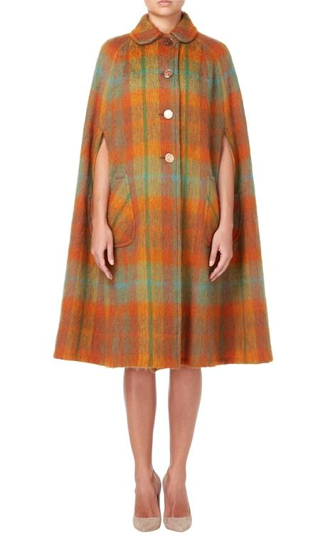The autumnal hues of this 1970s Strathtay cape make this perfect for cold days and weekends in the country. Constructed in orange, brown and green checked mohair, the cape fastens with buttons to the front and features a peter pan collar and