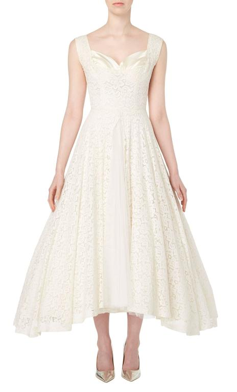 A stunning option for a wedding or summer party, this Jean Patou haute couture dress is the epitome of chic! Constructed in ivory lace, the dress features a sweetheart neckline with a pleated satin bust. The lace of the skirt is split up the front