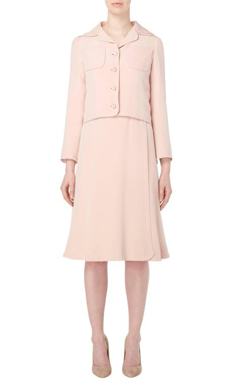 A gorgeous piece of haute couture, this Guy Laroche dress suit constructed in pale pink silk, is perfect for daytime events. The sleeveless dress has an extremely flattering cut, skimming the body and flaring into a softly pleated skirt. The belt