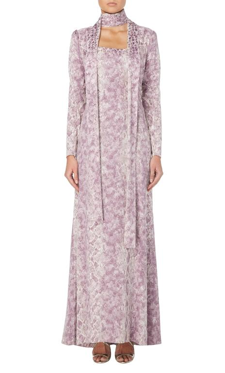 A beautiful and dramatic piece of haute couture by the great Yves Saint Laurent, this exceptional dress is made of pure silk, printed with a python skin pattern in lilac upon a rich ivory background. Gently shaped and darted at the waist to enhance