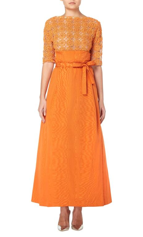 A vibrant orange Sybil Connolly ensemble, consisting of a wool crochet top and silk skirt, this beautiful two-piece will work for formal Events and summer parties alike. The top features a boat neckline that scoops lower in the back, and
