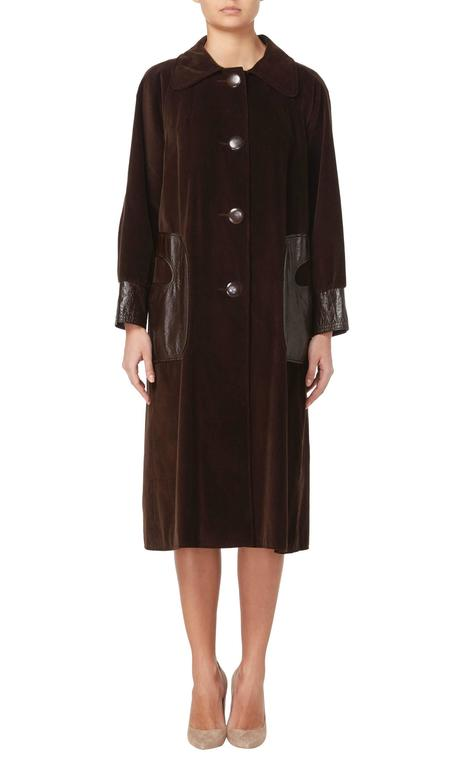 This Pierre Cardin coat is an amazing piece! Constructed in brown corduroy, the coat features an exaggerated collar and fastens to the front with overscale buttons. The pockets and cuffs are in a contrasting brown patent leather, while a wool lining