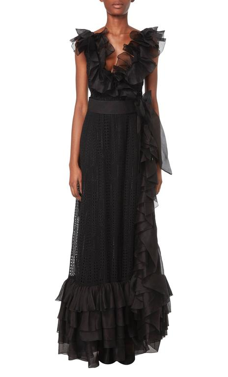 This dramatic Chanel haute couture dress is constructed in beautiful black silk georgette broderie anglaise, with a lining in the skirt and bust for opacity. The wrap front creates a flattering low-cut neckline, while a black organza belt with a bow