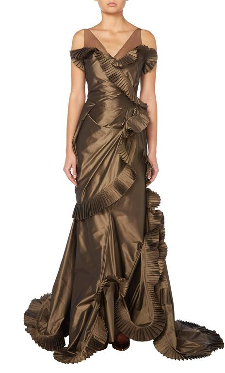 An eye-catching example of John Galliano for Christian Dior, this gown is constructed in brown silk taffeta and has a Far Eastern inspiration with its ruffled edging of micro-pleated silk taffeta and shoulder straps of bronze silk tulle.