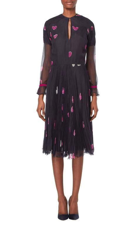 This beautiful Thea Porter couture dress features a romantic pink heart print by the textile artist Hannah Meckler. Constructed in dark blue silk chiffon, the dress features smocking on the shoulders and keyhole cutout on both the front and back.
