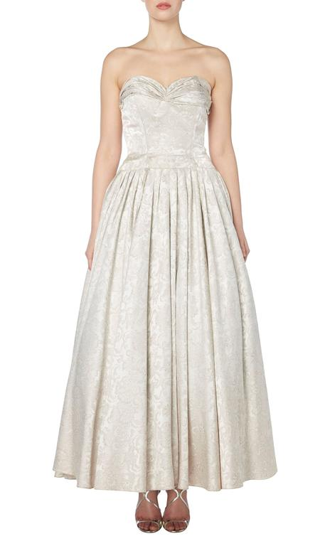 This stunning strapless gown is a rare example of haute couture by Lanvin herself. Perfect for a formal event or a wedding dress, the gown is constructed in pure silk with an abstract floral motif and features a gathered neckline and internal