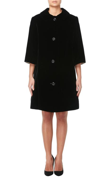An incredible piece of Dior haute couture, this coat was designed while Yves Saint Laurent was head designer at the fashion house. Constructed in sumptuous black velvet and lined in contrasting ivory silk, the coat has a swing shape, making it