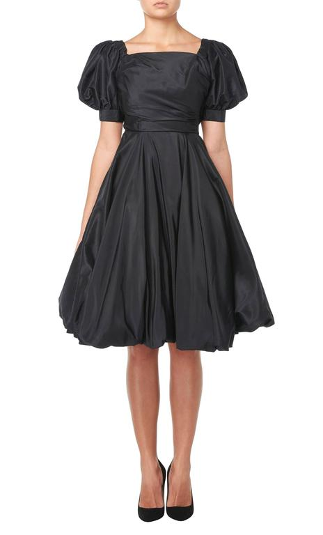 A fun take on the classic LBD, this puffball dress is a great choice for parties! Constructed in black silk, the dress features over scale puffed sleeves and a square neckline, while the skirt flares out from the waistline and gathers around the hem