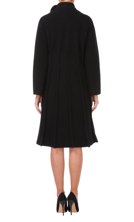 An amazing example of Pierre Cardin's modernist aesthetic, this black wool coat has a fantastic silhouette. Inverted seam detailing from the waist down creates a pleated effect, while a circle motif on the standing collar is indicative of Cardin's