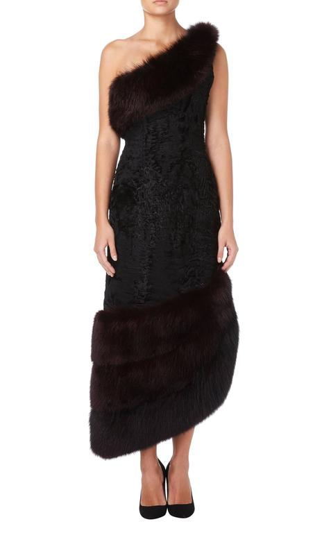 Constructed in black broadtail with a brown fox fur trim Featuring a side split Zip fastening to the side and hook and eye fastenings to the shoulder Excellent condition with the original lining and fastenings Professionally dry cleaned and