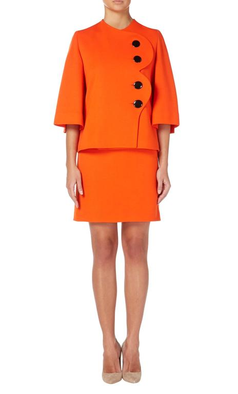 This bold Pierre Cardin skirt suit will make a colourful choice for the office or a daytime event. Constructed in vibrant orange wool, the jacket features split sleeves and a scalloped edge to the front, fastening with four overscale black buttons.