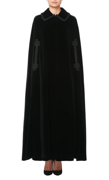 A dramatic evening ensemble, this Jean Patou two-piece is made up of a full-length cape and maxi skirt in matching black velvet. The cape features a collar and a single hook and eye fastening at the neck, allowing a glimpse of the outfit beneath.