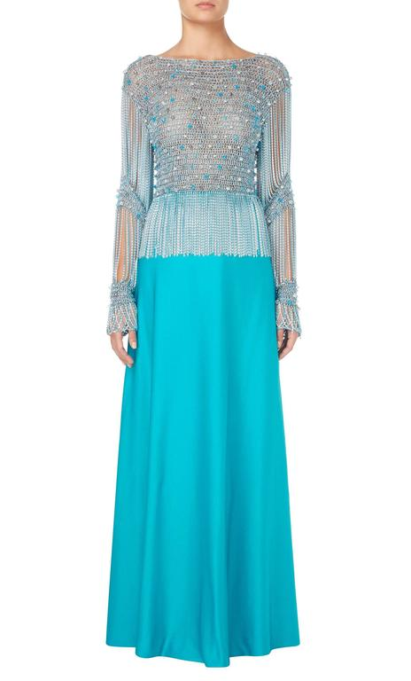 This incredible Azzaro ensemble, consisting of a metallic crop top and turquoise maxi skirt, is the ultimate in summer party dressing. The top is constructed in a metallic blue and silver knit and embellished with clear, blue and pearlescent beads,