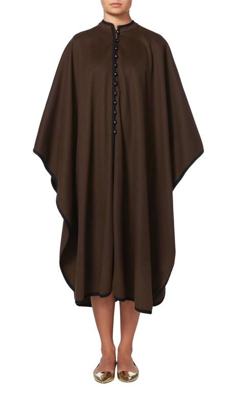This Yves Saint Laurent cape is a fantastic coverup for cold winter days. Constructed in brown wool and featuring a contrasting black braid, the cape has a standing collar and buttons to the front. Throw on over jeans for weekends in the country or