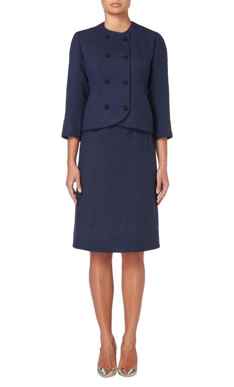 Introduce haute couture into a work wear wardrobe with this chic Balenciaga skirt suit. Constructed in navy wool, the double-breasted jacket fastens to the front with black beaded buttons and features a round neckline and three-quarter length