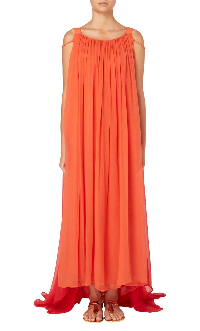 Constructed in layers of orange silk chiffon, this Yves Saint Laurent haute couture maxi dress features wide shoulder straps and a round neckline, plunging lower to the back. A layer of red chiffon creates a Watteau back, pooling into a train at the