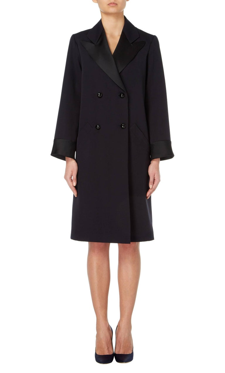 A fantastic example of Yves Saint Laurent's 'Le Smoking' look, this double-breasted coat is constructed in navy wool and features black satin lapels and cuffs. Fastening to the front with faceted buttons, the coat is sharply tailored with padding at