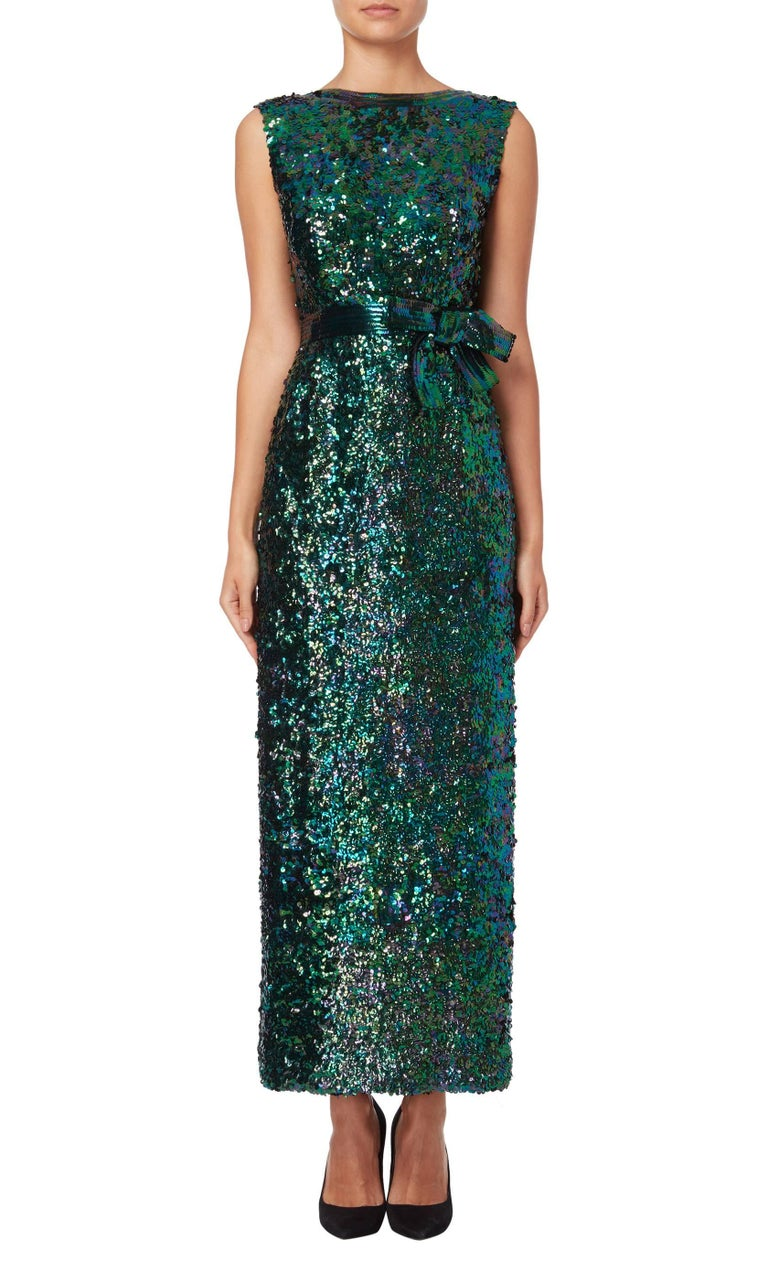 This elegant Norman Norell 1960's gown is adorned with green, blue and purple sequins and features a sequined bow to the waist. A stunning low cut back is met with a short tie to the small of the back