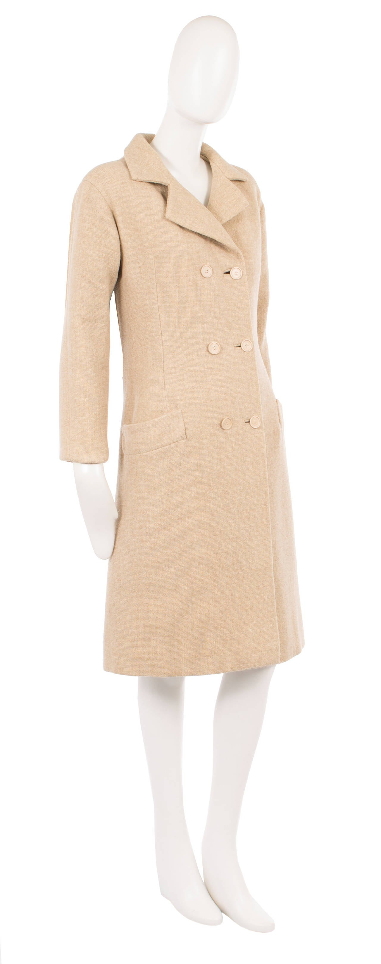 This sharply tailored haute couture coat by Balenciaga for his Eisa label will be sure to become a wardrobe staple. Constructed in a gorgeous shade of oatmeal wool the double-breasted coat features a double lapel collar and a half belt to the rear.
