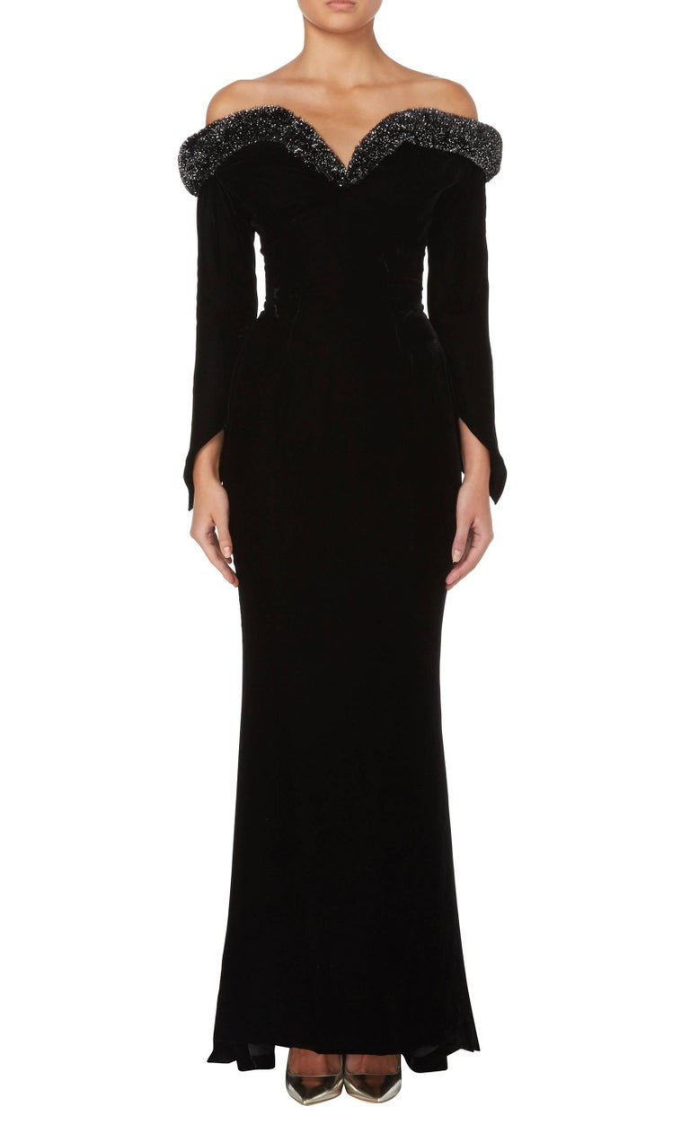 An incredible example of Thierry Mugler's sculptural designs, this black velvet gown sits off the shoulder with a silver lurex trim over the bust. The corseted bust adds support, while the velvet fabric skims the body seductively, falling into a