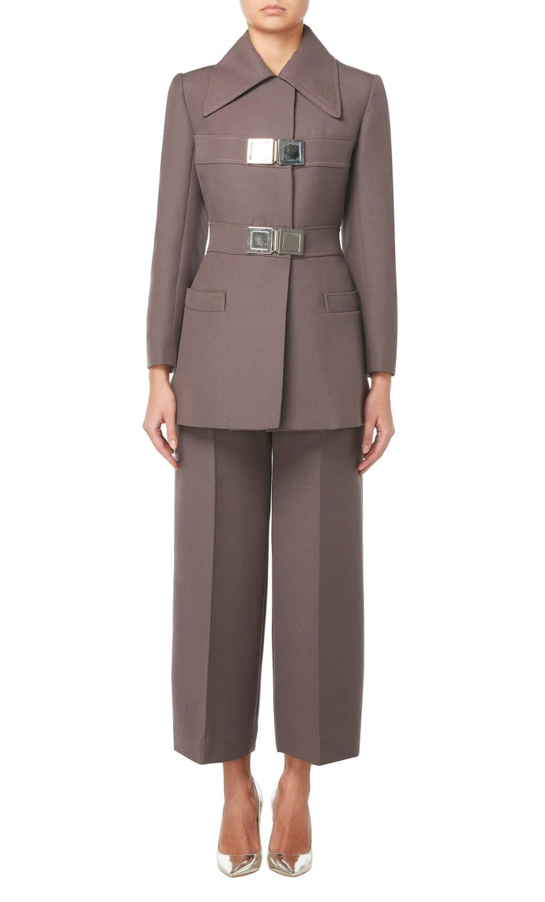 This sharply tailored, military-inspired trouser suit by Jean Patou will make a great alternative to traditional office wear. Constructed in brown wool, the suit is comprised of a jacket and straight cut trousers. With an exaggerated collar, the