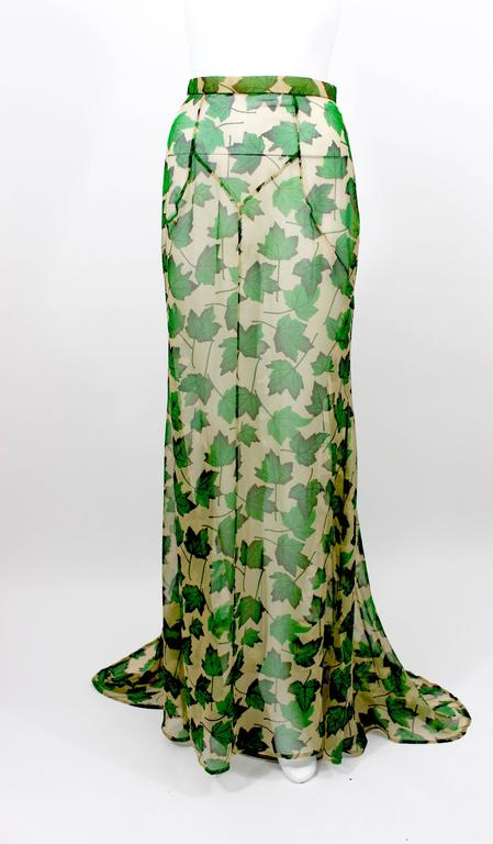 A beautiful figure flattering gown skirt with a train from Dolce & Gabbana. Fashioned from transparent beige silk chiffon with a vivid green and black falling leaves print throughout. 