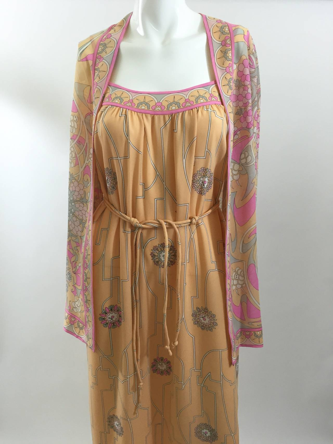 Stunning and ethereal Emilio Pucci light as a feather silk chiffon dress set.   The print of the dress is in soft pale colors of pink, white, gray and light cantaloupe.  Small flowers in different sizes  and designs dot the dress. Each flower's