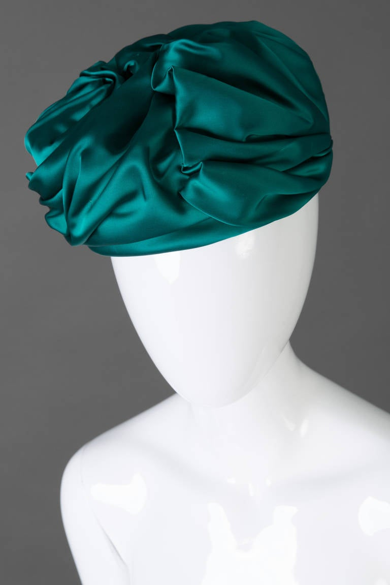 Stunning vintage Christian Dior Silk Turban.  The color is true Emerald Green.  Gorgeous details of pleating, folding and twisting. Interior of the turban is lined with a netting fabric and trimmed in grosgrain ribbon. Excellent vintage