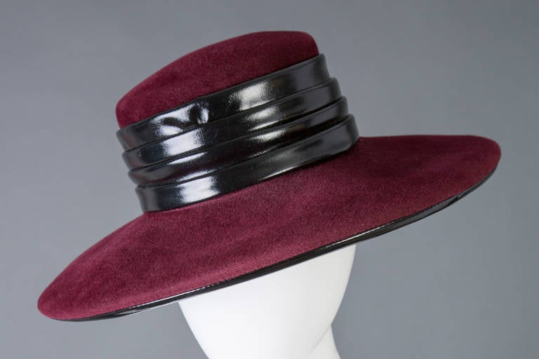 Elegant and Halston hat in burgundy wool felt with patent  trim. Around the crown is pleated black patent and the brim is piped as well. 1970s. Excellent condtion 15