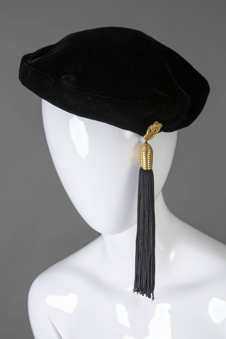 Yves Saint Laurent Black velvet beret with a tassel that measures seven inches in length. gold detail at the top of the tassel.