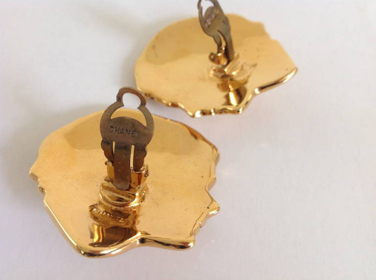 """These Chanel earrings are of a right and left profile of Mademoiselle Chanel looking at one another.   Each face has a pearl earring they are wearing . Condition is excellent.  They are signed """"Chanel"""" They measure in length from the center"""