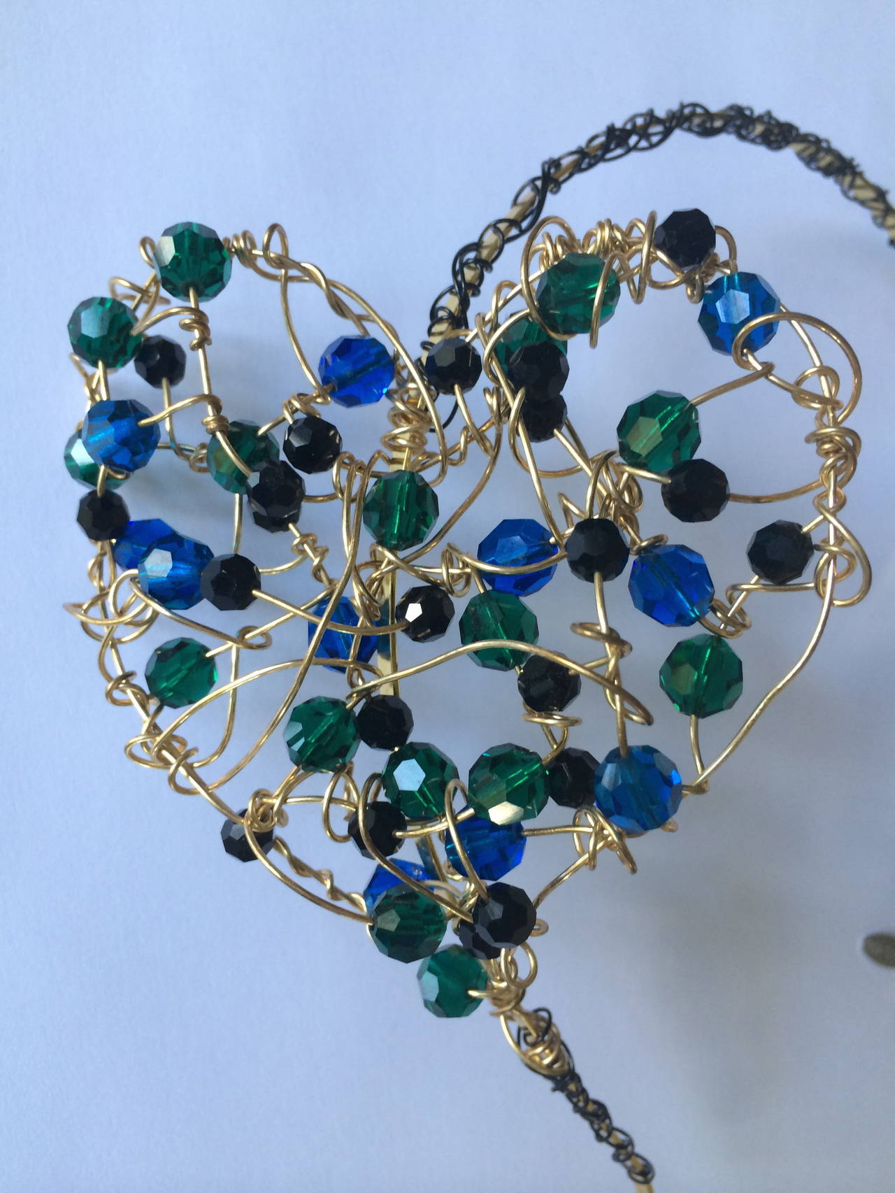Sculptural heart headband. Handmade with Swarovski crystal beads in hues of royal blue, emerald green and jet black.