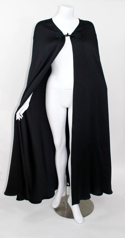 A Valentino Couture vintage cape.  Circa late 1970s. The jet black satin is extremely smooth and of superior quality. Embroidered toggle closures are hand sewn. The hem and frame of the cape are finished to perfection.  In Excellent condition aside