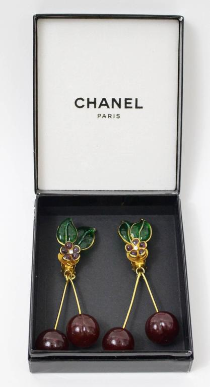 A magnificent pair of  Pate de Verre cherry earrings by Maison Gripoix for Chanel. Emerald green hand poured glass leaves and gold toned veins. Amethyst glass flowers with crystal paste centers and long dangling glass cherries.