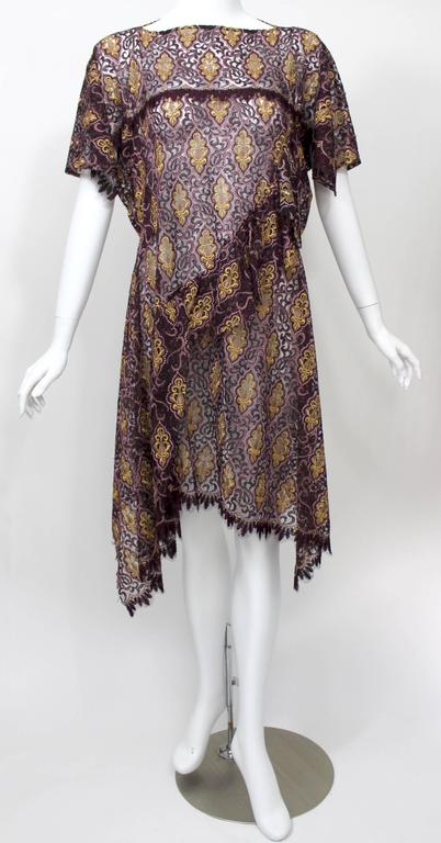 Lace gets the avant-garde treatment in this pretty spring/summer 2012 Junya Watanabe dress. The traditional fabric, here woven from richly hued burgundy, purple and gold threads into a gorgeous scroll motif, gets trimmed, draped, pintucked, ruffled