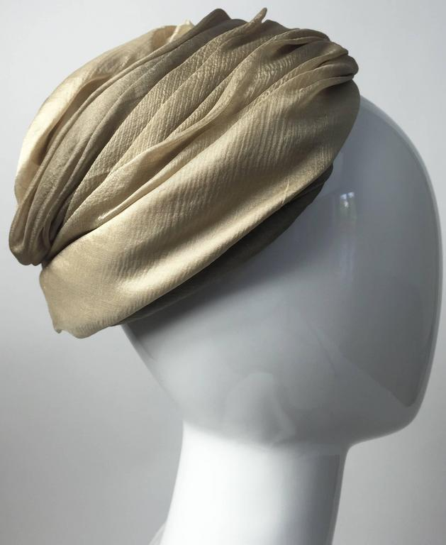 An exquisite early 1950s Christian Dior turban hat. Done in a soft silk chiffon in shades of taupe, beige and light golden ivory. The fabric is gently draped and pleated. Hand finished. Lined with a netting