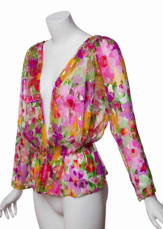 A stunning floral print flecked with gold and fuchsia throughout makes this Yves Saint Laurent blouse an incredible vintage find. Small and large blooms splash over a bed of white in a mouthwatering riot of poppy, violet, yellow and green, while