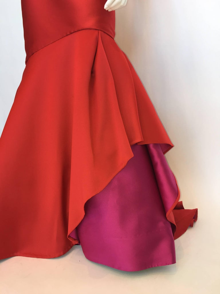 Monique Lhuillier Red Strapless Silk Gown. Back zip closure, long tail with Fuchsia underskirt and black tulle petticoat.  *ALL MEASUREMENTS TAKEN FLAT* Size Label: 12  Bust: 34.5
