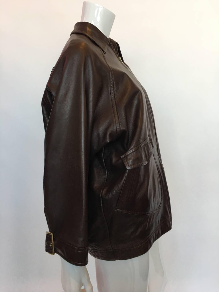 """1990s Isaac Mizrahi Oversized Dark Brown Leather Jacket with Built in Backpack  Size label: S  Measurements (taken flat) Shoulders (approx): 15"""" Sleeve (collar to wrist cuff): 26.5"""" Armpit to armpit: 24.5"""" Length: 25.5""""  Good"""